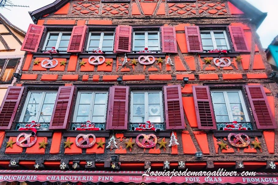 Casa típica alsaciana de color rojo decorada para Navidad en Ribeauville - Los viajes de Margalliver